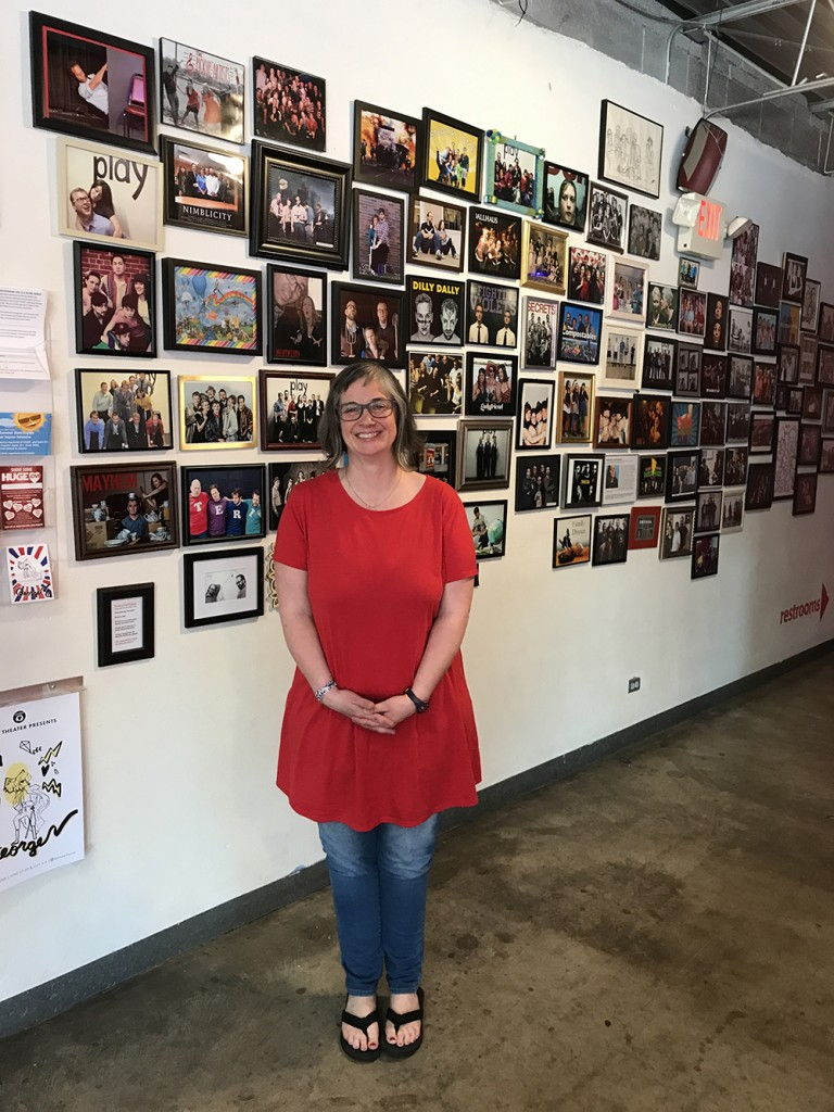 """HUGE co-founder Jill Bernard poses in front of a wall of photographs of improv troupes that have performed at the theater. """"Groups always ask how can they get our picture up here,"""" she said. """"We say, 'You have to go to Target, print it, get a frame and put it up here. It's not a juried exhibition.'"""" Photo by Zac Farber"""
